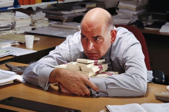 Mature-businessman-holding-arms-around-banknotes-piled-on-desk